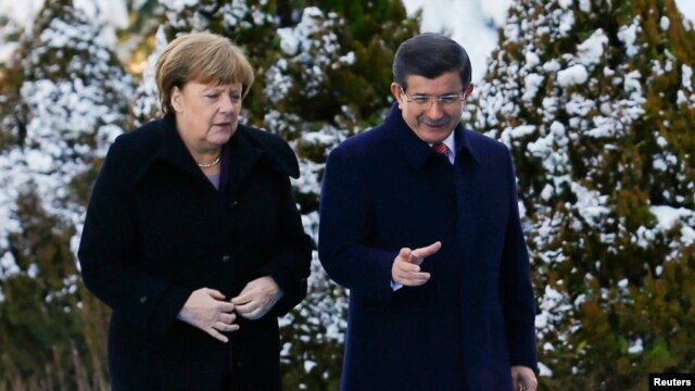 Turkish Prime Minister Ahmet Davutoglu (right) speaks with Angela Merkel during a welcoming ceremony for the German chancellor in Ankara on February 8.