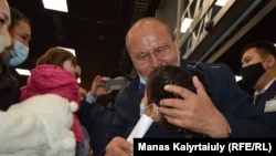 Raqyzhan Zeinolla embraces his granddaughter for the first time at the airport in Almaty on April 9.
