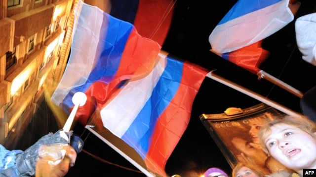 Pro-Kremlin youth activists wave the Russian flag as they rally in Moscow.