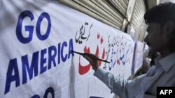 A Pakistani man prepares an anti-U.S. and anti-Facebook banner in Karachi earlier this week.