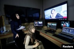 Khatira Ahmadi (R), 20, producer of Zan TV (women's TV) station, works in the editing room in Kabul on May 8.