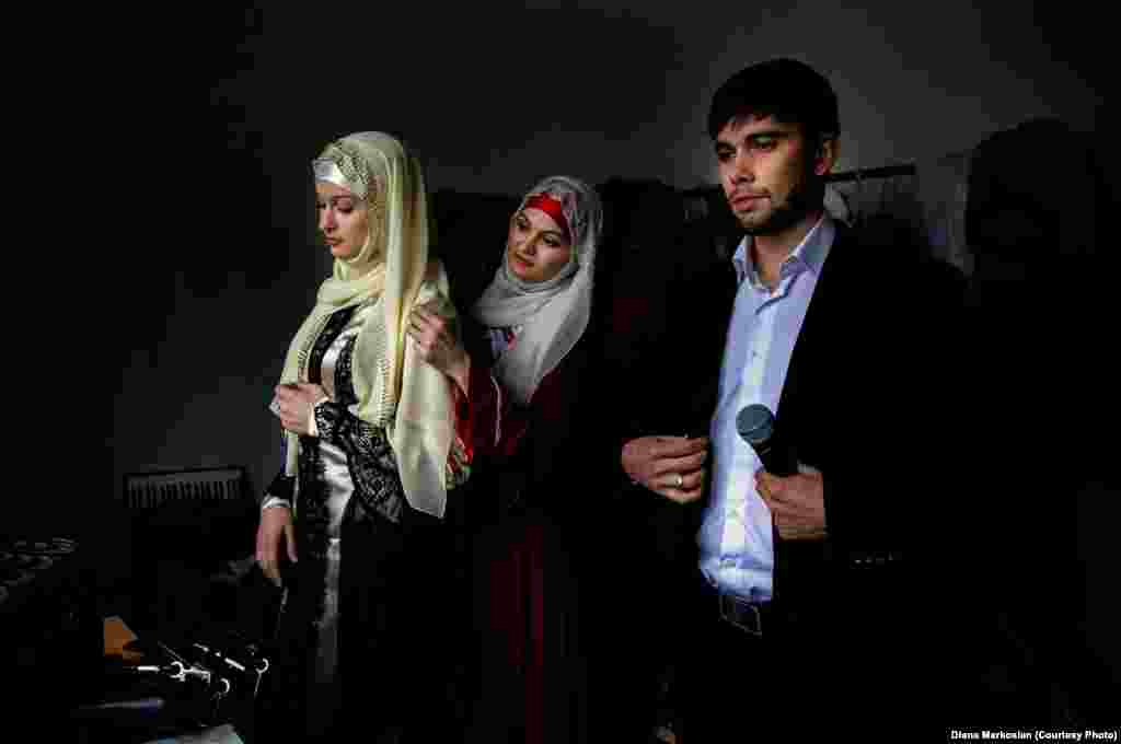 Chechen artists prepare backstage for their performance. All women in Chechnya must wear head scarves in public schools and state buildings. Celebrities were among the first to conform, making the head scarf a fashion statement.