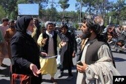 یک زن معترض افغان در مقابل یکی از نیروهای طالبان در جریان اعتراضهای روز پنجشنبه در هرات