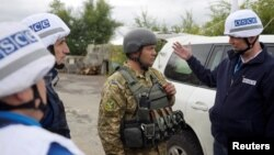Monitors from the Organization for Security and Cooperation in Europe (OSCE) speak with a Ukrainian serviceman as they visit the town of Zolote in the Luhansk region on September 26.