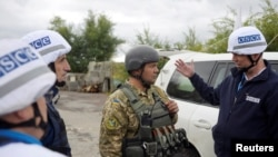 اعضای سازمان امنیت و همکاری در اروپا (OSCE) هنگام بازدید منطقه لوهانسک، 26 سپتمبر 2016 با یک سرباز اوکراینی صحبت میکنند.