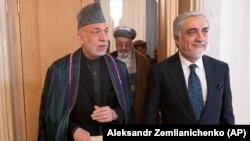Former Afghan President Hamid Karzai (L) and head of Afghanistan's High Council for National Reconciliation Abdullah Abdullah arrive at the conference in Moscow on March 18.