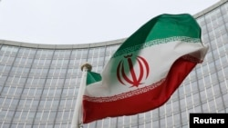 Флаг Ирана на фоне здания Агентства ООН по атомной энергии (МАГАТЭ) в Вене.