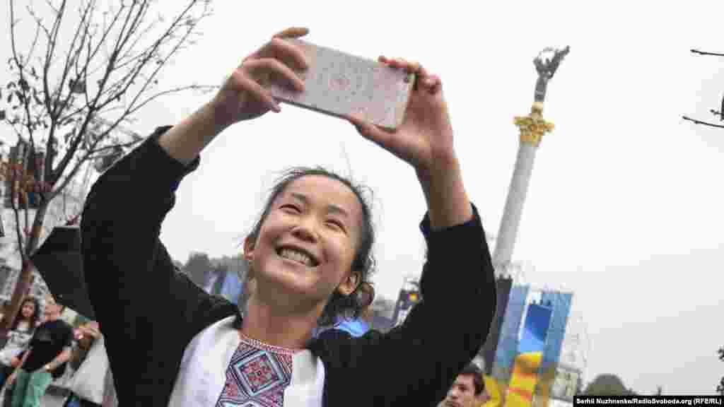 Туристка робить селфі на тлі монумента Незалежності