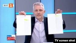 """Стоп кадър от предаването """"Още от деня"""" на БНТ от 33 юни 2021 г. Николай Хаджигенов показва документи, които, според него, доказват подслушването на политици."""