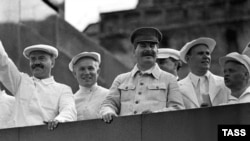 Солдан оңға: Вячеслав Молотов, Никита Хрущев және Иосиф Сталин Қызыл алаңдағы парадты тамашалап тұр. Мәскеу, 1936 жыл.