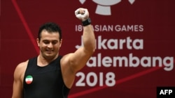 Sohrab Moradi of Iran celebrates after breaking the world record in the men's 94-kilogram class weightlifting event at the 2018 Asian Games in Jakarta on August 25.