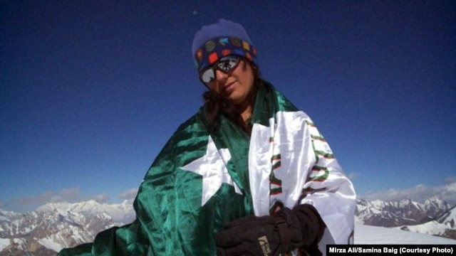 Mountaineer Samina Baig poses with a Pakistani flag during a previous climb.