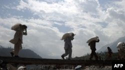 Pakistani flood affected victims carry relief goods through a damaged bridge in western Pakistan in September 2010.