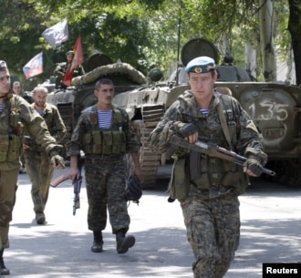 Ukraine -- Pro-Russian separatists walk past armoured personnel carriers (APC) near the urban settlement of Zaytsevo in the Donetsk region, July 20, 2015