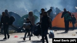Migrants in Bosnia carry their belongings near a border crossing with Croatia. (file photo)