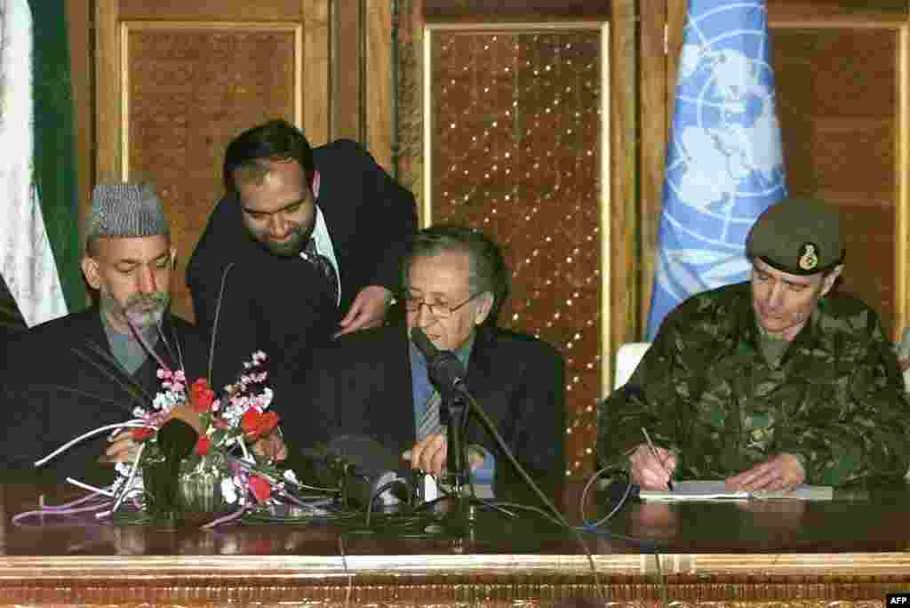 British Major General John McColl (right), UN special representative Lakhdar Brahimi (center), and Karzai during the January 4, 2002, signing of an agreement on the deployment of foreign troops on Afghan soil.