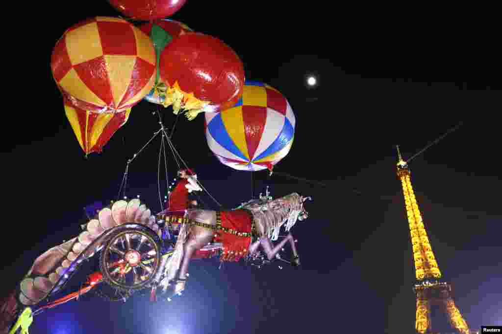 Helium-filled balloons suspend a Santa Claus figure riding a horse-drawn chariot made of balsa wood, created by artist Nasser Volant, near the Eiffel Tower in Paris. (Reuters/Charles Platiau)