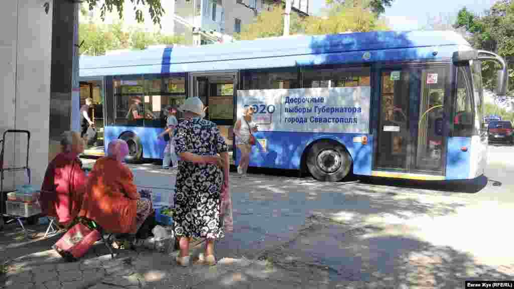 Пожилые женщины торгуют инжиром и виноградом на остановке общественного транспорта