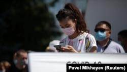 Люди в очереди перед мобильным пунктом тестирования в Алматы. 17 июня 2020 года.