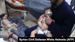 Unidentified volunteers give aid to children at a hospital following an alleged chemical attack on the rebel-held town, April 8, 2018