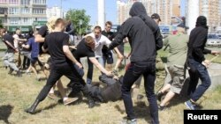 Protesters attack a policeman during the Equality March organized by the LGBT community in Kyiv in June 2015.