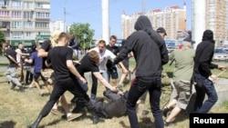 Группа людей нападает на полицейского во время так называемого «Марша равенства», организованного лесбиянками, геями, бисексуалами и транссексуалами (ЛГБТ) в Киеве. 6 июня 2015 года.