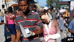 An injured woman is helped after being rescued in Port-au-Prince.