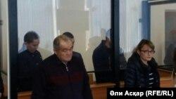 """Ақтөбеде """"Сирияға кетпек болды"""" деп айыпталған Нұрлан Өмірбеков пен оның екі серігі (артқы жақта) сот залында тұр. Ақтөбе, 25 қазан 2016 жыл."""
