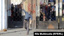 A man hurls an object during clashes between students and Egyptian security forces near Al-Azhar University in Cairo on December 27.