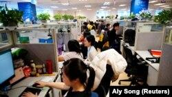 A Ctrip.Com online utazási iroda munkatársai dolgoznak Sanghajban egy, a kormány által újságíróknak szervezett munkahelybejárás közben, 2021. január 14-én.