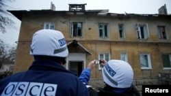 Ukraine -- An Organization for Security and Cooperation in Europe (OSCE) investigator takes pictures of a building after it was damaged by recent shelling in the western part of Donetsk, eastern Ukraine, November 27, 2014. REUTERS/Antonio Bronic (UKRAINE