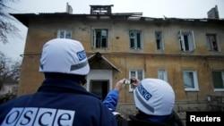 Представители ОБСЕ фотографируют дом, в который попал боевой снаряд. Донецк, ноябрь 2014 года. Иллюстративное фото.