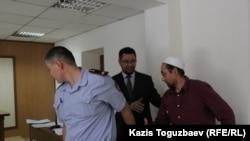 Адвокат Жандос Булхайыр (в середине) пытается пожать руку подсудимому Сакену Тулбаеву. Алматы, 16 июня 2015 года.