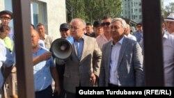 Омурбек Текебаев (слева, с мегафоном) и Дуйшонкул Чотонов на выходе из здания Первомайского райсуда Бишкека. 29 августа 2019 года.