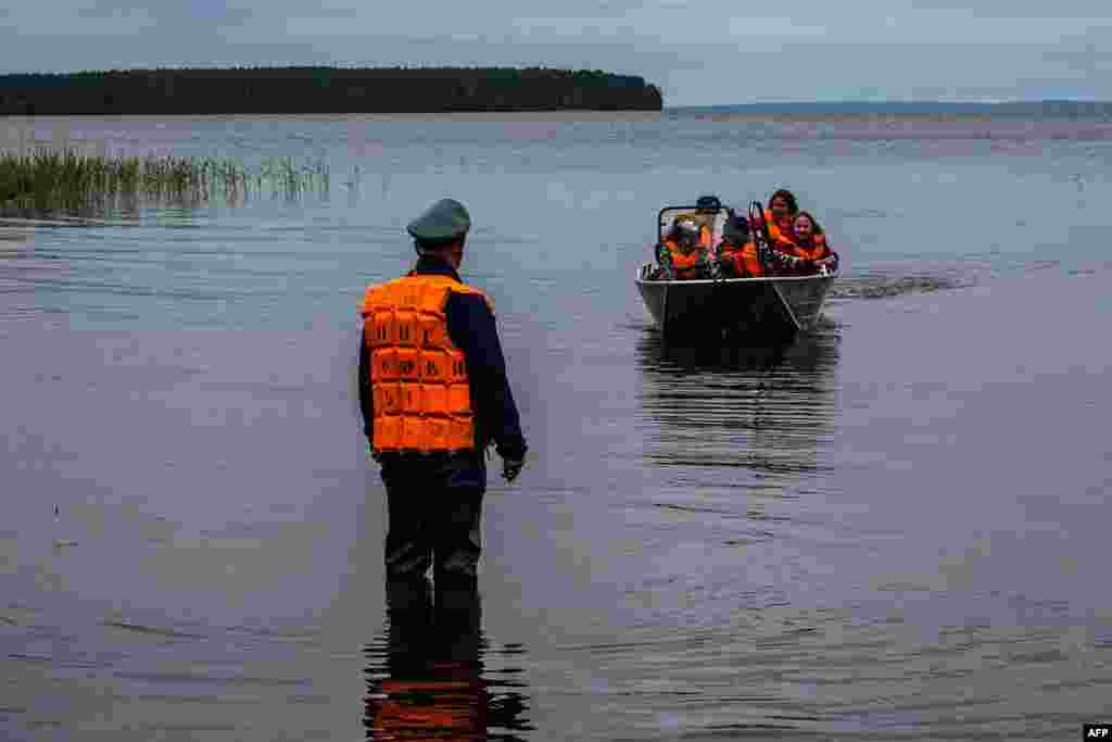 Emergency workers carry surviving children in a boat on Lake Syamozero in Russia's Karelia region on June 19. At least 14 died when two boats capsized on the lake at the weekend. (AFP)