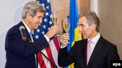 АҚШ мемлекеттік хатшысы Джон Керри (сол жақта) мен Молдова премьер-министрі Юрие Лянкэ шарап құйылған бокал көтеріп тұр. Молдова, 4 желтоқсан 2013 жыл.