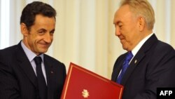 Kazakh President Nursultan Nazarbaev (right) exchanges documents at the end of a meeting with his French counterpart Nicolas Sarkozy in Astana.