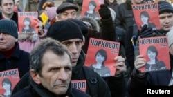 Протестующие вышли с фотографиями избитой журналистки к зданию МВД Украины. Киев, 26 декабря 2013 года.