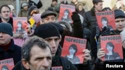 Protestuesit ukrainas me fotografitë e gazetares Tetyana Chornovil.