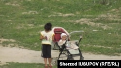 Девочка рядом с коляской, в которой сидит ребенок. Ошская область Кыргызстана. Иллюстративное фото.