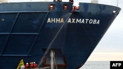 """Greenpeace activists attach themselves to the anchor of the Russian passenger ship, """"Anna Akhmatova,"""" in the Barents Sea on August 27."""