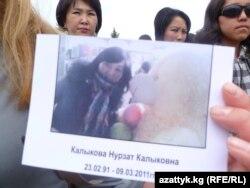 Участники акции протеста против кражи невест держат в руках фотографию девушки. Каракол, Кыргызстан, 18 мая 2011 года.