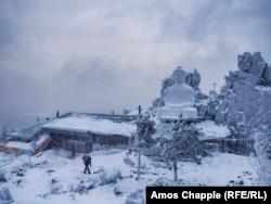Будист носи дърва покрай манастира Шедруб Линг. Тази сграда е в центъра на конфликта. Снимката е от декември 2016 г.