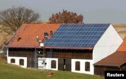 Muncitori instalând panouri solare pe o casă în Germania