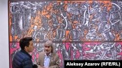 Казахстанский художник Оразбек Есенбаев общается с посетителем на фоне картины «16 мгновений зимы». Алматы, 10 апреля 2019 года.