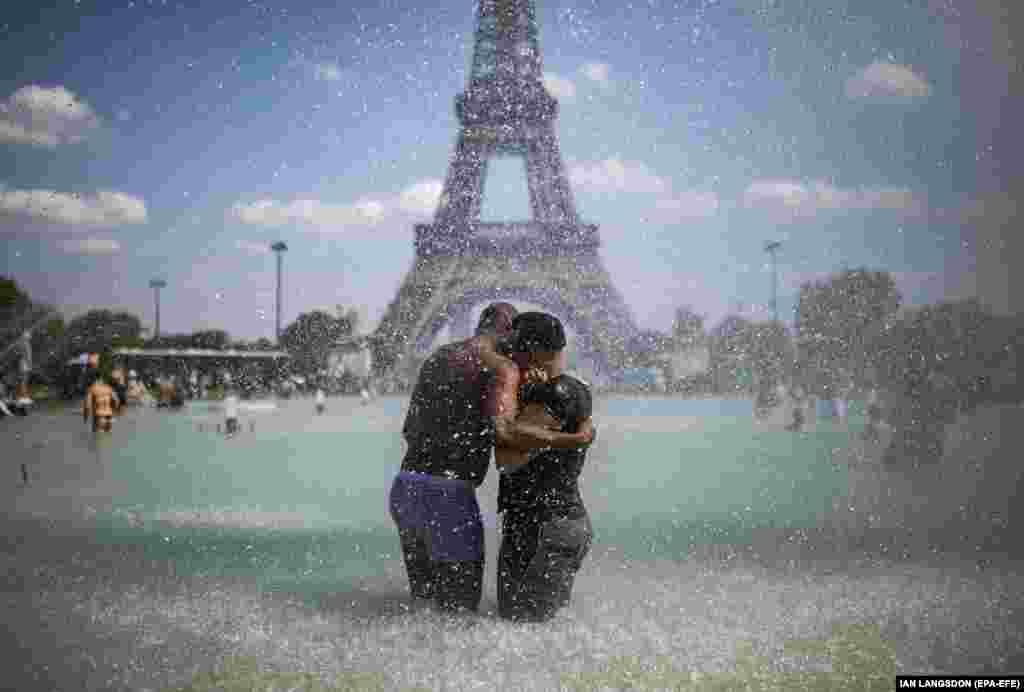 A couple cool down in the fountains of Trocadero, across from the Eiffel Tower, during a heatwave in Paris, France. (epa-EFE/Ian Langsdon)