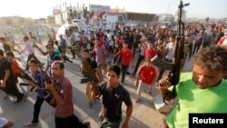 In Baghdad, members of a Shi'a militia parade through the streets.