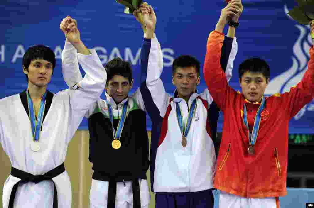 محمد باقری معتمد (از چپ دوم )؛ برنده مدال طلای رشته تکواندو در کنار رقیبانش - گوانگژو، چین