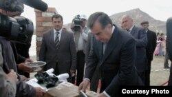 Президент Таджикистана Эмомали Рахмон закладывает капсулу под здание будущей электростанции.