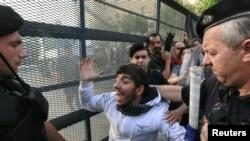 Демонстрант оказывает сопротивление полицейским у здания парламента. Афины, 15 июня 2011 года.